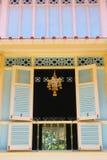 垂悬在黄色和蓝色大厦窗口的花诗歌选在公开区域 库存照片
