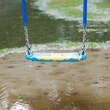 垂悬在水坑的塑料摇摆 免版税库存图片