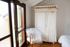 垂悬在绝尘室的美丽的新娘的礼服 免版税库存照片
