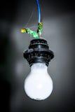 垂悬在黑弹药筒的白光电灯泡 图库摄影