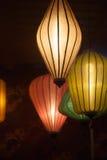 垂悬在黑暗中的4个五颜六色的中文报纸灯笼 免版税库存照片