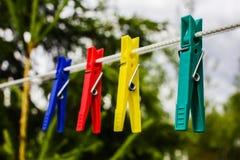 垂悬在绳索的五颜六色的晒衣夹 库存照片