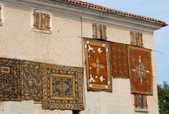 垂悬在绳索的六个红地毯 免版税库存图片