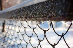 垂悬在滤网篱芭的冰柱对角行  免版税库存照片
