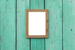 垂悬在绿色老木破裂的墙壁上的木制框架 图库摄影