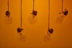 垂悬在黄色背景的白炽光电灯泡 图库摄影