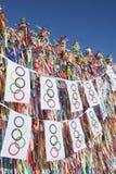 垂悬在巴西愿望丝带前面的奥林匹克旗子旗布 免版税库存照片