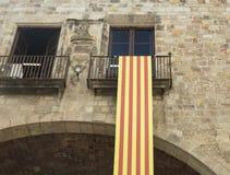 垂悬在从t的一个阳台的卡塔龙尼亚的国旗细节  库存照片