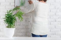 垂悬她的在墙壁上的妇女剪影 女性艺术家评估她的绘画表现,尝试它在白色砖墙上,自由温泉 免版税图库摄影