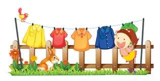 垂悬她的衣裳的夫人在庭院附近用兔子 免版税库存照片