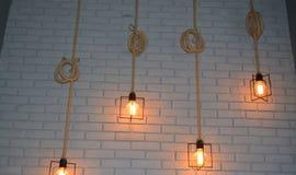 垂悬异乎寻常的灯在墙壁 库存照片