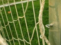 垂悬弯曲的足球网,白色足球橄榄球网 在橄榄球操场的草在背景中 不锈的框架 免版税库存照片