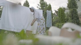 垂悬成熟主妇的妇女在一好日子洗涤了在晒衣绳的干净的洗衣店她的房子外 ??  股票视频