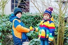 垂悬树的两个小孩男孩鸟房子哺养的在冬天 免版税图库摄影
