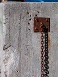 垂悬沿墙壁的老生锈的重链 库存照片