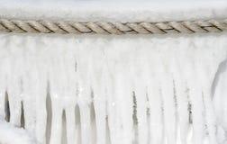 垂悬港口绳索的冰墙壁 库存图片