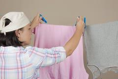 垂悬湿干净的布料的可爱的妇女烘干在晾衣绳 免版税库存照片