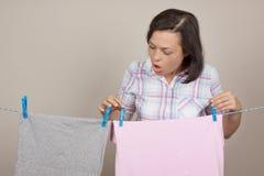 垂悬湿干净的布料的可爱的妇女烘干在晾衣绳 库存图片