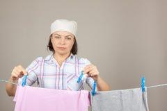 垂悬湿干净的布料的可爱的妇女烘干在晾衣绳 库存照片