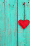 垂悬由在古色古香的小野鸭蓝色木背景的丝带的红色心脏 库存照片