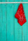 垂悬由在古色古香的蓝色木背景的绳索边界的红色班丹纳花绸 免版税库存图片