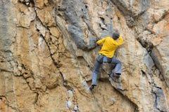 垂悬由峭壁的年轻男性登山人 免版税库存图片