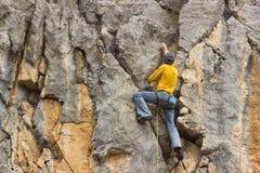 垂悬由峭壁的年轻男性登山人 免版税图库摄影