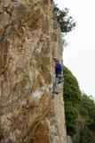 垂悬由峭壁的年轻男性登山人 库存图片