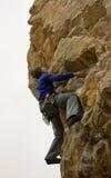 垂悬由峭壁的年轻男性登山人 免版税库存照片