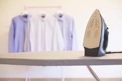 垂悬由干燥和铁决定的洗涤的衬衣上室内木内部 免版税库存图片