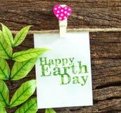 垂悬由红色心脏的愉快的世界地球日纸笔记在木截去 库存图片