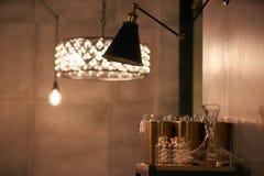 垂悬电灯泡和壁灯的光亮枝形吊灯 图库摄影
