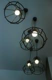 垂悬电灯泡的葡萄酒在灰色室 库存照片