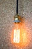 垂悬电灯泡的葡萄酒装饰在棕色墙壁上 免版税库存图片