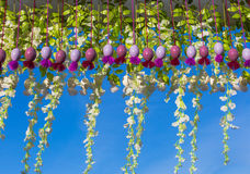 垂悬的五颜六色的复活节彩蛋和花卉装饰在蓝天背景 免版税图库摄影