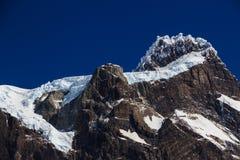垂悬的冰川,紧贴对峰顶在其中一座在托里斯台尔潘恩国家公园巴塔哥尼亚的山顶部 免版税库存图片