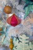 垂悬的发光的金子和五颜六色的圣诞节缠绕与闪亮金属片和 免版税库存照片