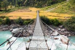 绳索垂悬的吊桥在尼泊尔 免版税库存照片
