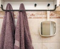 垂悬的对象在卫生间里:两块毛巾和一个白色镜子 免版税库存照片