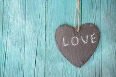 垂悬的心脏和绿松石木背景在乡村模式 免版税库存照片