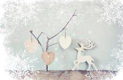 垂悬的木心脏和在木背景的木雨鹿装饰 与雪花覆盖物的减速火箭的被过滤的图象 免版税库存照片