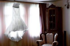 垂悬的美丽的白色婚礼礼服 免版税图库摄影