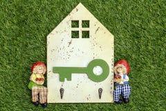 垂悬的钥匙的减速火箭的木板和在绿草的男孩和女孩玩偶 图库摄影