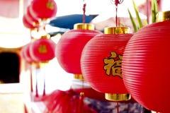 垂悬红色中国灯行,在中国文本的选择聚焦 免版税库存图片