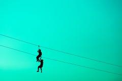 垂悬缆绳绳子的剪影人 库存照片