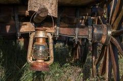 垂悬老生锈的葡萄酒油灯笼的灯在日志 免版税库存图片