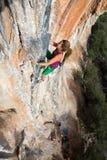 垂悬高在五颜六色的岩石墙壁上的极端体育运动员 免版税库存图片