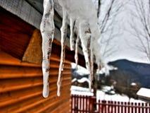 垂悬从一个木房子的屋顶的冰柱 免版税库存图片