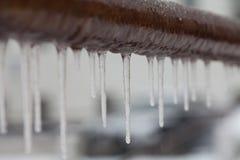 垂悬从一个棕色管子的冰柱 冻结的水和金属表面,冬时概念 选择聚焦浅深度  图库摄影