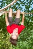 垂悬从一棵树的青少年的男孩在夏天庭院里 库存图片